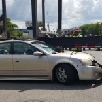 Car trapped under logging truck on 701